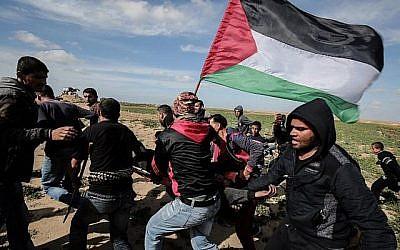Les Palestiniens aident à évacuer un manifestant blessé durant des affrontements avec les soldats israéliens près de Khan Yunis le long de la clôture frontalière entre Israël et le sud de la bande de Gaza, le 9 mars 2018 (Crédit :  AFP PHOTO / SAID KHATIB)