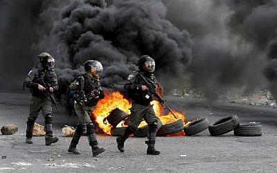 Les gardes-frontières israéliens dans une rue durant des affrontements avec des manifestants palestiniens protestant contre le transfert de l'ambassade américaine à Jérusalem, dans la ville de Ramallah, en Cisjordanie, le 9 mars 2018 (Crédit :  / AFP PHOTO / ABBAS MOMANI)