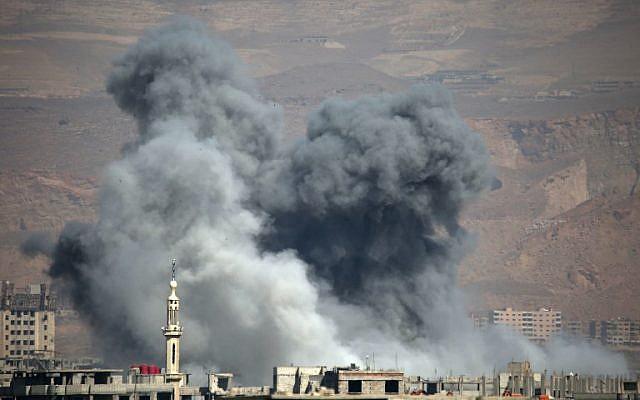 De la fumée s'élève suite aux bombardements du gouvernement dans la ville d'Arbin, contrôlée par les rebelles, dans l'enclave de la Ghouta orientale assiégée aux abords de la capitale de Damas le 11 mars 2018 (Crédit : / AFP PHOTO / Amer ALMOHIBANY)