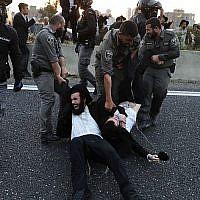 La police évacue des manifestants ultra-orthodoxes qui bloquent une route lors d'une manifestation contre l'enrôlement de l'armée dans la ville de Bnei Brak, près de Tel-Aviv, le 12 mars 2018 (Crédit : AFP PHOTO / Ahmad GHARABLI)