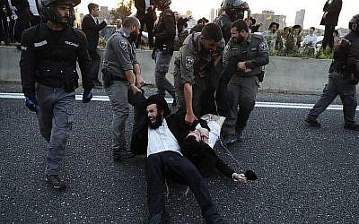 La police enlève des manifestants ultra-orthodoxes qui bloquent une route lors d'une manifestation contre l'enrôlement de l'armée dans la ville de Bnei Brak, près de Tel-Aviv, le 12 mars 2018 (Crédit : AFP PHOTO / Ahmad GHARABLI)