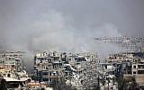 Fumée s'élève suite aux bombardements du gouvernement syrien sur la ville assiégée par les rebelles de Harasta, dans la région de la Ghouta orientale, à la périphérie de Damas, le 12 mars 2018 (Crédit : AFP PHOTO)