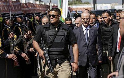 Le Premier ministre palestinien Rami Hamdallah, deuxième à droite, escorté de ses gardes du corps, est accueilli par les forces de police du Hamas, à gauche, à son arrivée à Gaza le 13 mars 2018. (AFP Photo/Mahmud Hams)