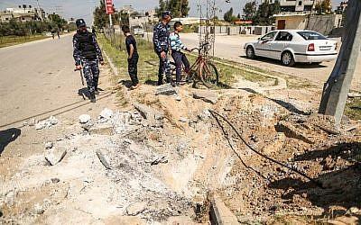 Des membres des forces de sécurité du Hamas inspectent le cratère laissé sur le site d'une explosion qui a visé le convoi du Premier ministre palestinien lors de sa visite dans la bande de Gaza le 13 mars 2018. (AFP/MAHMUD HAMS)