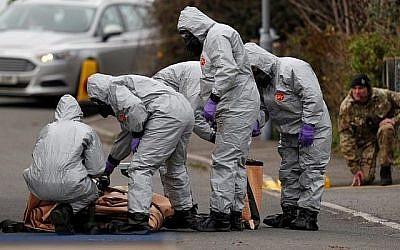 Des militaires britanniques portant une combinaison de protection travaillent pour évacuer un véhicule lié à l'attaque de l'agent neurotoxique du 4 mars à Salisbury, dans le sud-est de l'Angleterre, le 14 mars 2018. (Adrian DENNIS/AFP)