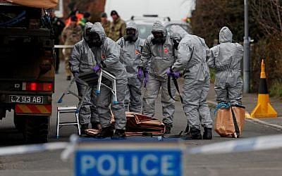 Des militaires britanniques portent des combinaisons de protection afin d'enlever un véhicule lié à l'empoisonnement du 4 mars à Salisbury (Crédit : AFP / ADRIAN DENNIS)