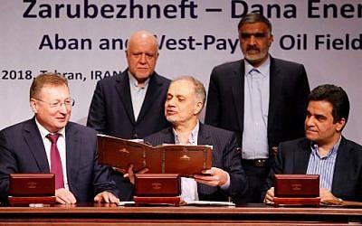 Le ministre iranien du Pétrole, Bijan Namadar Zanganeh (au fond à gauche) et le président de la Commission iranienne de l'énergie Fereydoun Hasanwand (au fond à droite), accompagnés de Segey Kudryashov, directeur général de Zaubezhneft (à gauche), Ali Kardor, directeur exécutif de la Compagnie pétrolière nationale iranienne (au centre), et Mohammad Iravani, président de Dana Energy (à droite), signent un accord pétrolier à Téhéran, le 14 mars 2018 (PHOTO AFP / ATTA KENARE)