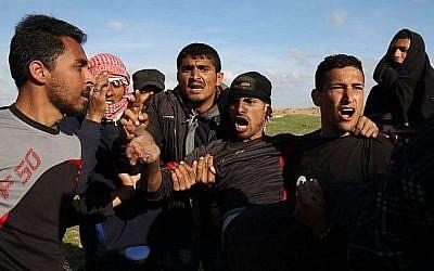 Des hommes palestiniens évacuent un manifestant blessé lors d'affrontements avec les troupes israéliennes le long de la barrière frontalière près de Khan Yunis dans le sud de la bande de Gaza le 16 mars 2018. (AFP Photo/Said Khatib)