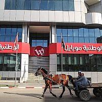 Des Palestiniens montent une charrette tirée par un cheval devant la porte fermée du siège social de la société Wataniya Mobile dans la ville de Gaza le 17 mars 2018. (AFP PHOTO / MAHMUD JAMBON)