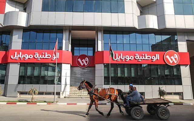 Des Palestiniens montent une charrette tirée par un cheval devant la porte fermée du siège social de la société Wataniya Mobile dans la ville de Gaza le 17 mars 2018. (AFP PHOTO / MAHMUD HAMS)