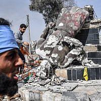 """Des rebelles syriens soutenus par les Turcs retirent une corde de la statue de """"Kawa"""", le forgeron qui était une figure centrale dans une légende kurde sur la célébration du nouvel an de Norouz, après l'avoir détruite dans la ville d'Afrin dans le nord de la Syrie le 18 mars 2018. (AFP PHOTO / BULENT KILIC)"""