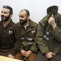 Romain Franck (D), 24 ans, travailleur au consulat de France, et les Palestiniens Moufak al-Ajluni (G) et Mohamed Katout (C) comparaissent devant le tribunal de la ville israélienne de Haïfa le 19 mars 2018, pour faire face à des accusations de contrebande d'armes à Gaza (Crédit : AFP / JACK GUEZ)