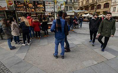 Des touristes sur le trottoir de la zone pédestre de la place Wenceslas à Prague, une rue formée d'anciennes tombes d'un cimetière juif abandonné, le 15 mars 2018 (Crédit :/ AFP PHOTO / Michal CIZEK)