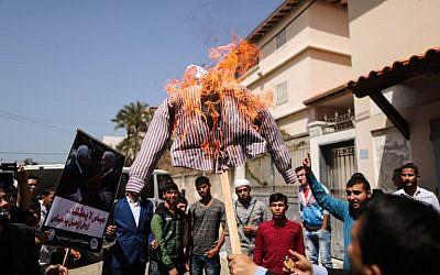 Des Palestiniens brûlent un mannequin représentant le président palestinien Mahmoud Abbas lors d'une manifestation dans la ville de Gaza le 21 mars 2018 (Crédit : AFP / MAHMUD HAMS)