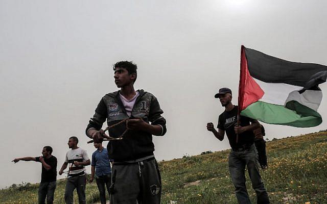 Un manifestant palestinien jette des pierres sur les soldats israéliens lors d'affrontements près de la frontière avec Israël à Khan Younès, dans le sud de la bande de Gaza, le 23 mars 2018. (AFP PHOTO / DIT KHATIB)