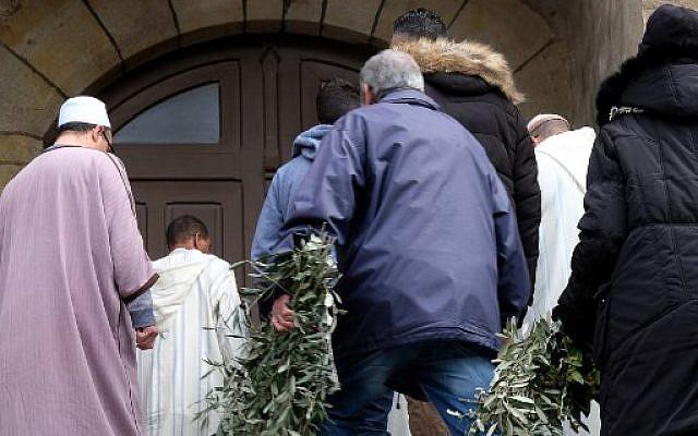 Des personnes portent des couronnes de rameaux d'olivier à l'église Saint Etienne de Trebes, dans le sud-ouest de la France, pour un service commémoratif le 25 mars 2018, deux jours après un attentat dans lequel quatre personnes ont été tuées (AFP PHOTO / ERIC CABANIS)