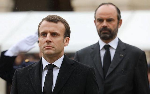 Emmanuel Macron, Édouard Philippe en arrière-plan à l'hommage national organisé par la France pour Arnaud Beltrame, mort en héros à Trèbes, le 28 mars 2018 (Crédit : AFP/MARIN/POOL)