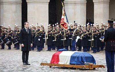Le président français Emmanuel Macron (à gauche) se tient près du cercueil du lieutenant-colonel Arnaud Beltrame, après lui avoir décerné à titre posthume la médaille de commandant de l'Ordre de la Légion d'honneur lors d'une cérémonie nationale le 28 mars 2018 à l'Hôtel des Invalides à Paris. (Ludovic MARIN / POOL / AFP)