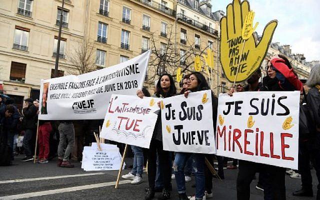 Des politiciens et d'autres personnes se tiennent derrière des bannières alors qu'ils se préparent à participer à une marche blanche à Paris le 28 mars 2018, à la mémoire de Mireille Knoll, une femme juive de 85 ans assassinée chez elle. (Crédit : AFP / ALAIN JOCARD)