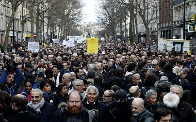 Les participants marchent derrière des banderoles tenant des pancartes lors d'une marche silencieuse à Paris en mémoire de Mireille Knoll, une Juive de 85 ans assassinée chez elle dans ce que la police a qualifié d'attaque antisémite (Crédit : François Guillot / AFP)