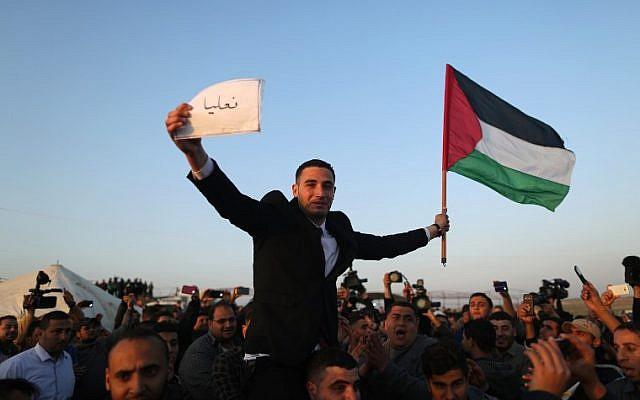 Les Palestiniens portent un jeune marié qui brandit le drapeau palestinien et tient une pancarte avec le nom du village de sa famille en IsraPel à la frontière de Gaza avec Israël (dans le fond), à l'est de Jabalia, le 29 mars 2018, avant la tenue d'un camp de protestation de six semaines (Crédit : AFP PHOTO / MAHMUD HAMS)