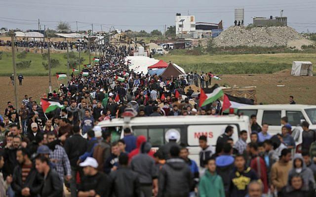 Les Palestiniens franchissent une ville de tente dressée le long de la frontière avec Israël, à l'est de Gaza City, pour commémorer la Journée de la terre (Crédit : AFP/ MAHMUD HAMS)