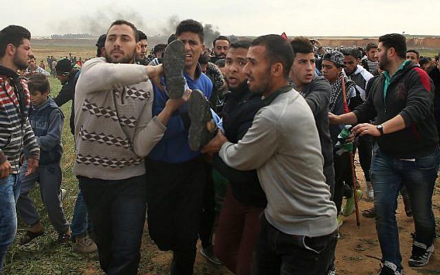 Une photo prise le 30 mars 2018 montre un jeune Palestinien transporté sur un brancard après avoir été blessé lors d'une manifestation à proximité de la frontière à l'est de Jabalia, lors de la journée palestinienne de commémoration de la Terre.  (Crédit : AFP/ Mohammed ABED)