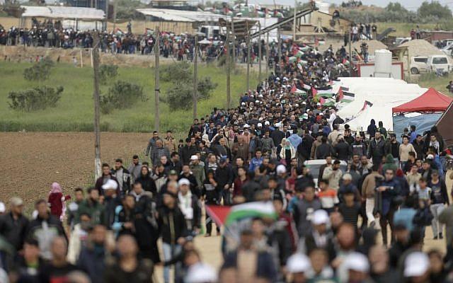 Les Palestiniens franchissent une ville de tentes dressées le long de la frontière avec Israël, à l'est de Gaza City, pour commémorer la Journée de la terre (Crédit : AFP/ MAHMUD HAMS)