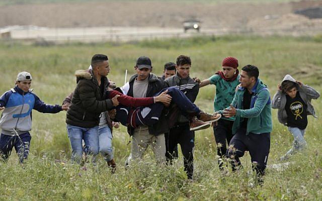 Un jeune Palestinien blessé est porté par d'autres manifestants alors qu'ils fuient lors d'affrontements à la frontière avec Israël à l'est de la ville de Gaza commémorant la Journée de la Terre, le 30 mars 2018 (Crédit : AFP PHOTO / MAHMUD HAMS)