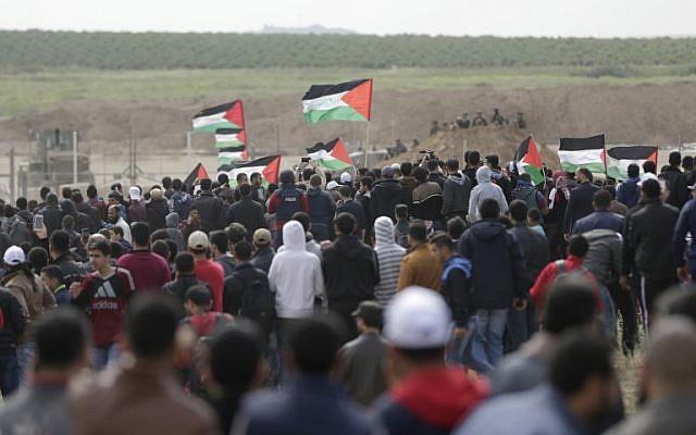Les Palestiniens défilent devant une tente érigée le long de la frontière avec Israël à l'est de la ville de Gaza dans la bande de Gaza pour commémorer la Journée de la Terre, le 30 mars 2018 (Crédit : AFP PHOTO / MAHMUD HAMS)