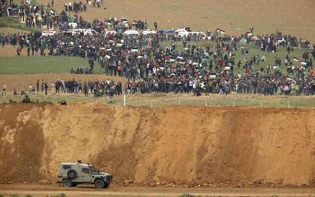 Une photo prise le 30 mars 2018 du kibboutz israélien sud de Nahal Oz de l'autre côté de la bande de Gaza montre des Palestiniens participant à une manifestation pour commémorer la Journée de la Terre, avec des véhicules militaires israéliens au premier plan (Crédit : AFP PHOTO / Jack GUEZ)