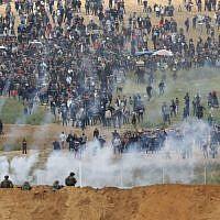 Une photo prise le 30 mars 2018 depuis le kibboutz de Nahal Oz de l'autre côté de la bande de Gaza montre des Palestiniens participant à une manifestation pour commémorer la Journée de la Terre (Crédit : AFP / Jack GUEZ)