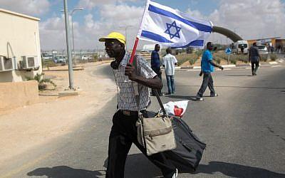 Un migrant africain clandestin marche avec un drapeau israélien suite à sa libération du centre de détention de Holot dans le désert israélien du Negev, le 25 août 2015 (Crédit : AFP PHOTO/MENAHEM KAHANA)