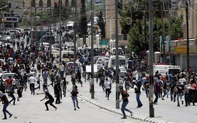 Des Palestiniens lancent des pierres sur les forces de sécurité israéliennes lors des affrontements de la Journée de la Nakba dans la ville de Bethléem, en Cisjordanie, le 15 mai 2017. (AFP Photo/Thomas Coex)
