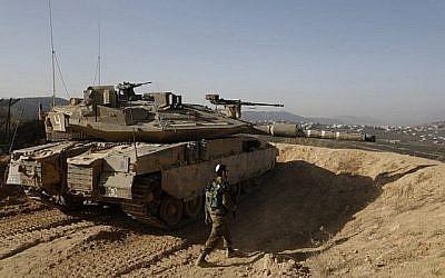 Une photo prise le 16 novembre 2017 montre un soldat israélien marchant à côté d'un char dans une position de l'armée surplombant le sud du Liban dans la ville israélienne de Metula, au nord d'Israël, le long de la frontière israélienne avec le Liban. (AFP PHOTO / MENAHEM KAHANA)