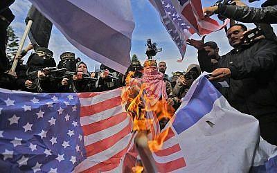 Des partisans du groupe terroriste du Jihad islamique palestinien brûlent des drapeaux américains durant une manifestation à Gaza City contre la décision du président Donald Trump de reconnaître  Jérusalem comme capitale d'Israël, le 11 décembre 2017 (Crédit : AFP Photo/Mohammed Abed)