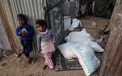 Des enfants palestiniens se tiennent à côté de sacs d'aide alimentaire fournis par l'agence des Nations Unies pour les réfugiés palestiniens dans le camp de réfugiés de Rafah, dans le sud de la bande de Gaza, le 24 janvier 2018. (AFP Photo/Said Khatib)