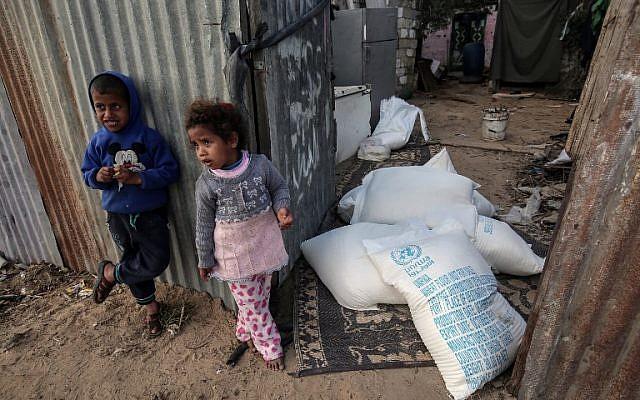 Des enfants palestiniens se tiennent à côté de sacs d'aide alimentaire fournis par l'agence des Nations Unies pour les réfugiés palestiniens dans le camp de réfugiés de Rafah, dans le sud de la bande de Gaza, le 24 janvier 2018. (Crédit : AFP/Said Khatib)