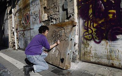 L'artiste de rue née en Israël et qui vit à New York Sara Erenthal dessine l'un de ses visages emblématiques de femme dans la ville côtière israélienne de Tel Aviv, le 28 janvier 2018 (Crédit :   AFP PHOTO / MENAHEM KAHANA)