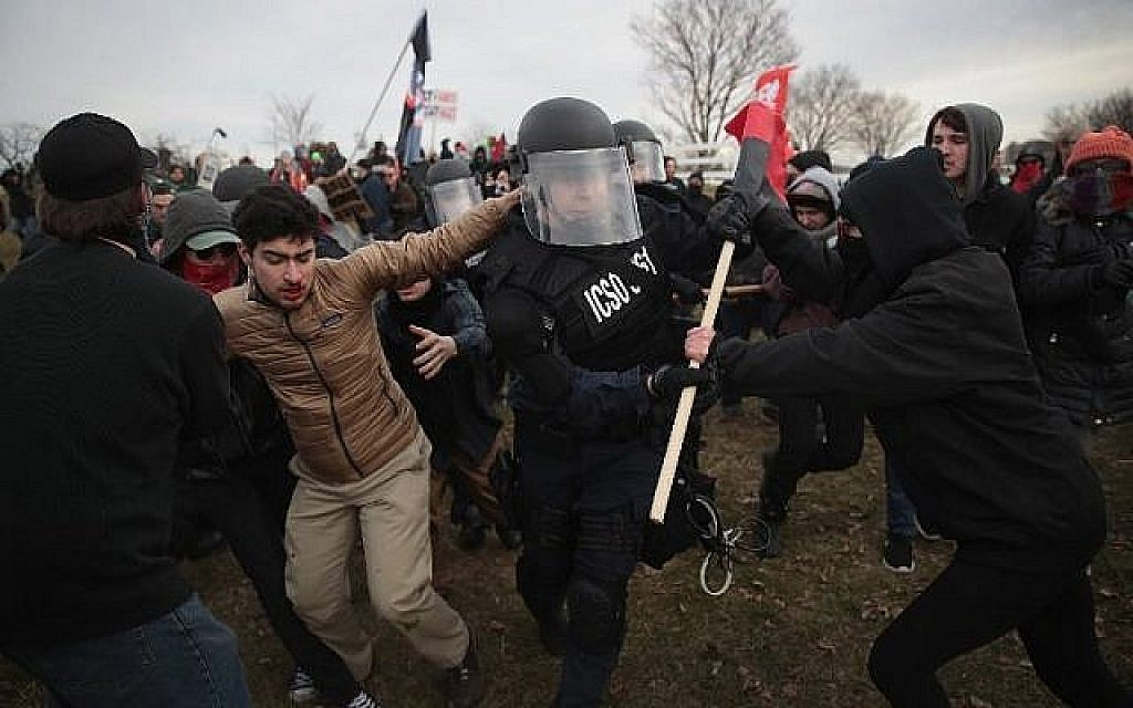 "Les policiers s'affrontent avec des manifestants alors qu'ils escortent les gens à un discours prononcé par le nationaliste blanc Richard Spencer, qui a popularisé le terme ""alt-right"", à la Michigan State University le 5 mars 2018 à East Lansing, Michigan. (Scott Olson/Getty Images/AFP)"
