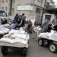 Des Palestiniens collectent des colis d'aide dans un centre de distribution alimentaire des Nations unies, à Khan Yunis, dans le sud de la bande de Gaza, le 28 janvier 2018 (Said Khatib / AFP)