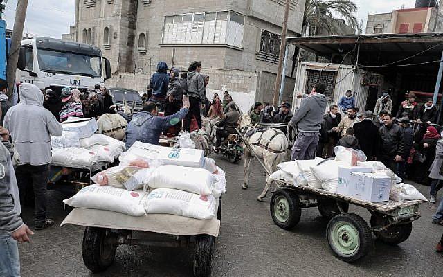 Des Palestiniens collectent des colis d'aide dans un centre de distribution alimentaire des Nations unies, à Khan Yunis, dans le sud de la bande de Gaza, le 28 janvier 2018 (Crédit : Said Khatib / AFP)