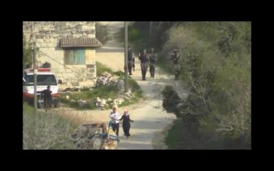 Des soldats israéliens jettent une grenade incapacitante en direction d'un couple palestinien portant un bébé (Capture d'écran : Yesh Din)