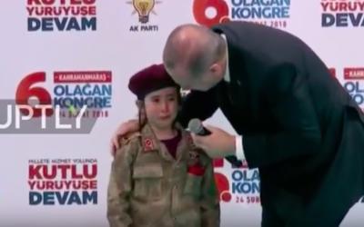 Le président turc Recep Tayyip Erdogan aux côtés d'une fillette portant un uniforme des forces spéciales turquesen larmessur une estrade lors d'un meeting de l'AKP, le 28 février 2018 (Crédit : capture d'écran YouTube)