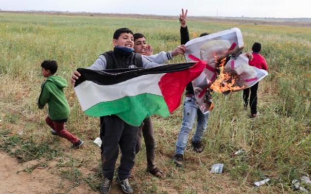 Des enfants de la bande de Gaza agitent un drapeau palestinien et brûle un drapeau à l'effigie de Donald Trump, le 30 mars 2018 (Crédit : Said Khatib/AFP)