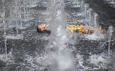 Des enfants jouent dans une fontaine d'eau lors d'une chaude journée d'été près de la tour de David dans la vieille ville de Jérusalem. (Yonatan Sindel / Flash90)