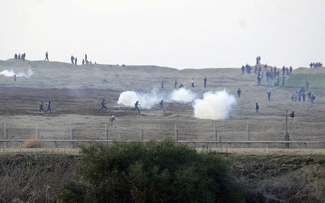 Des manifestants palestiniens près de la clôture de la frontière israélienne avec la bande de Gaza alors que les soldats israéliens utilisent des gaz lacrymogènes, 3 janvier 2014. (David Buimovitch/Flash90)