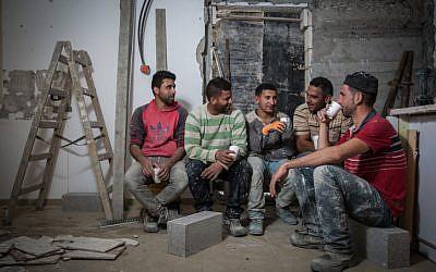Des ouvriers en bâtiment palestiniens du village d'Abadiya en Cisjordanie, pendant une pause-café dans une maison en cours de rénovation dans l'implantation juive d'Alon, au sud de Jérusalem, le 16 février 2016 (Crédit : Hadas Parush / Flash90)