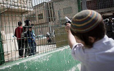 Illustration : Des habitants d'implantation israéliens taquinent des Palestiniens alors que la parade annuelle marquant la fête juive de Pourim passe par la ville divisée de Hébron, en Cisjordanie, le 1er mars 2018 (Crédit :   Hadas Parush/Flash90)