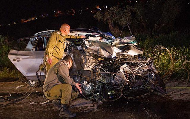 Des soldats israéliens inspectent une voiture sur les lieux où deux soldats israéliens ont été tués et deux autres blessés lors d'un attentat terroriste  à la voiture-bélier près de Mevo Dotan, en Cisjordanie, le 16 mars 2018. (Meir Vaknin/Flash90)